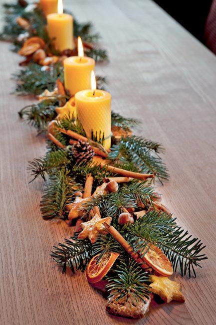 Idée de déco de Noël avec des branches de sapin et des oranges séchées
